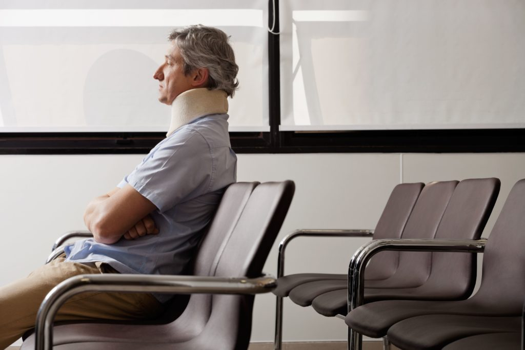 Injured man with neck brace sitting in waiting room