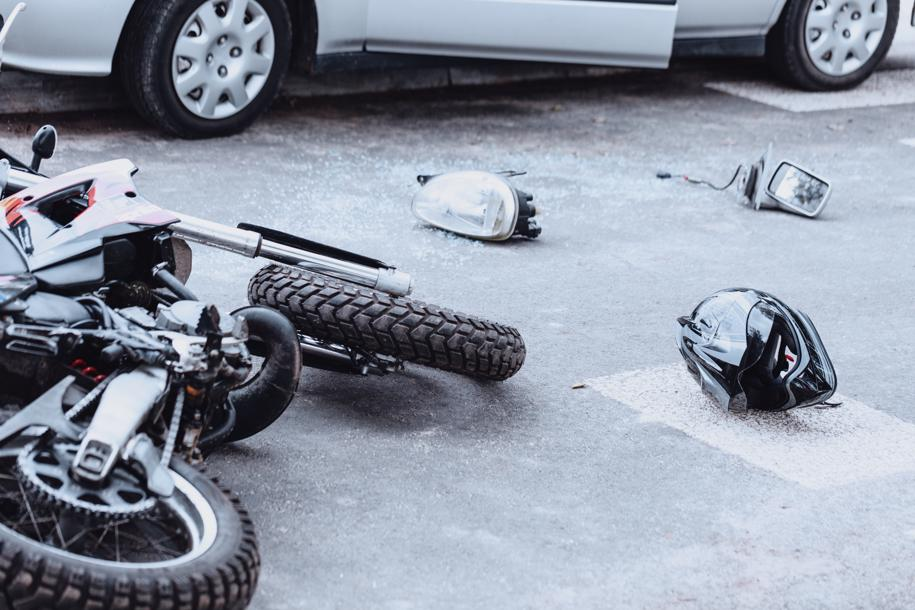 A motorcycle lying on its side in the road after an accident.